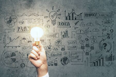 Businessman hand holding bulb and drawing global business marketing plan. Trade and business analysis concept.