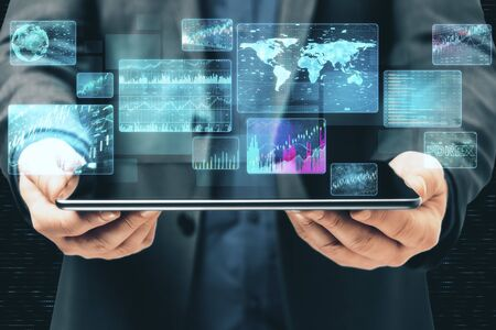 Businessman holding tablet with digital business interface. Global business and media concept. Close up