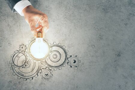Businessman hand holding light bulb with drawing cogs on a concrete wall background. Teamwork and idea concept Stok Fotoğraf