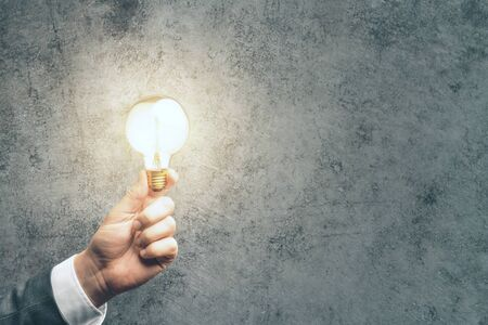 Businessman hand holding bulb on concrete background. Business success and startup concept. Banque d'images