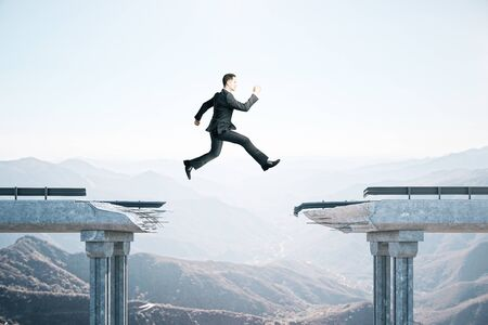 Businessman jumping over the gap in the bridge on mountain background. Business and challenge concept.