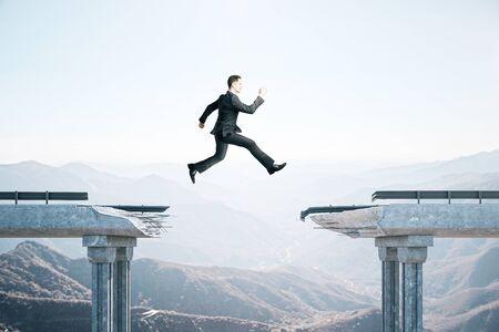 Homme d'affaires sautant par-dessus l'écart dans le pont sur fond de montagne. Concept d'entreprise et de défi.