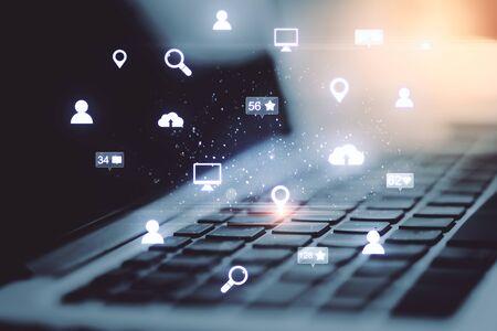 Ordinateur portable avec des icônes de réseau social rougeoyantes. Concept mondial d'entreprise et de médias.