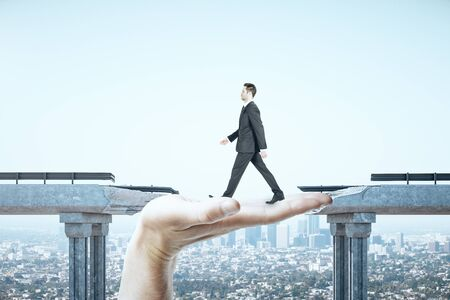 Businessman walking over gap in bridge on megapolis city view background. Business and challenge concept.