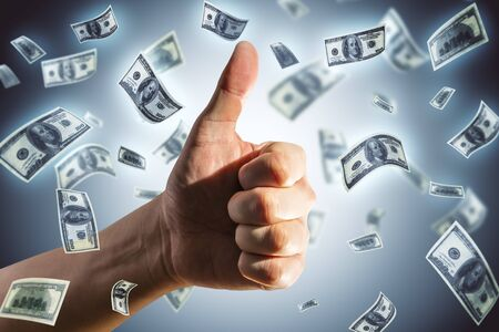 Hand showing thumb up and falling dollar banknotes. Business and financial success concept.