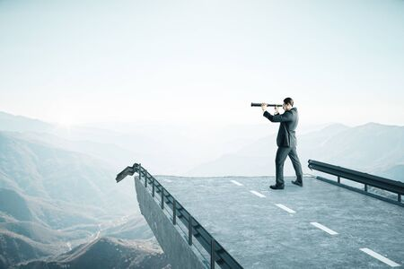 Businessman with telescope standing on destroyed bridge and looking to mountain. Business and challenge concept. Reklamní fotografie