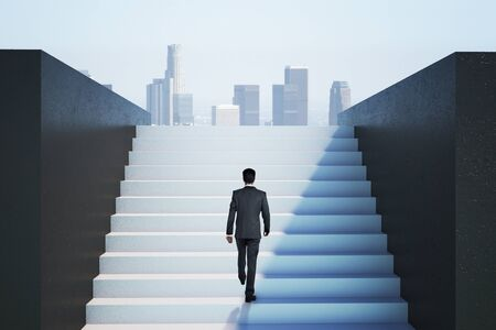 Businessman in suit climbing on ladder to success on city view background. Leadership and success concept Foto de archivo