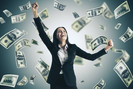 Happy businesswoman and falling dollar bills. Business and financial success concept.