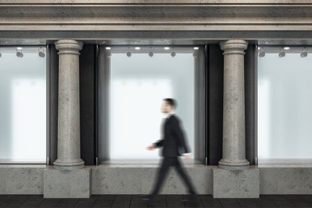 Businessman walking down street near shop window with blank poster. Advertisement and retail concept. Mock up,