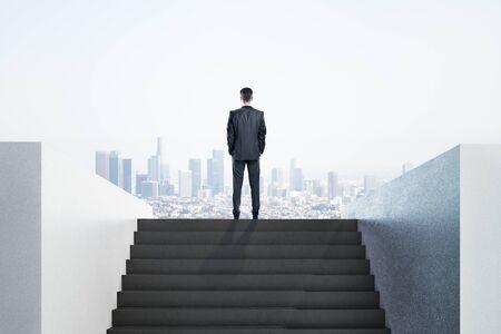 Geschäftsmann im Anzug, der auf Leiter steht und zum Hintergrund der Stadtansicht schaut. Führungs- und Erfolgskonzept