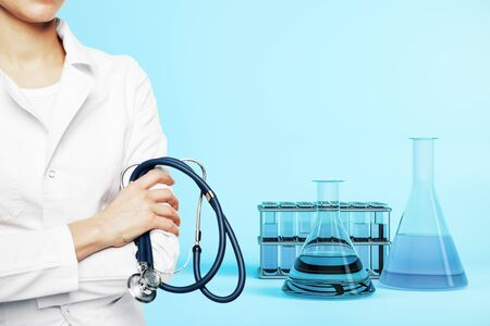 Woman doctor with stethescope and test tubes on blue background. Close up. Medical and healthcare concept Imagens