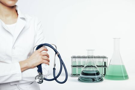 Woman doctor with stethescope and test tubes on white background. Close up. Medical and healthcare concept