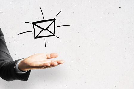 Businessman hand holding drawing e-mail symbol on white wall background. Business and information communication technology concept