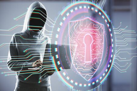 Hacker holding laptop with antivirus shield hologram. Web safety and cyberspace concept. Close up