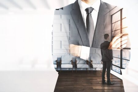 Businessman standing in waiting room interior with double exposure of businessman in suit. Leadership and job concept