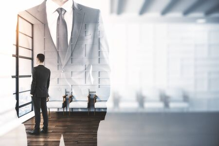 Businessman standing in waiting room interior with double exposure of businessman in suit. Leadership and success concept