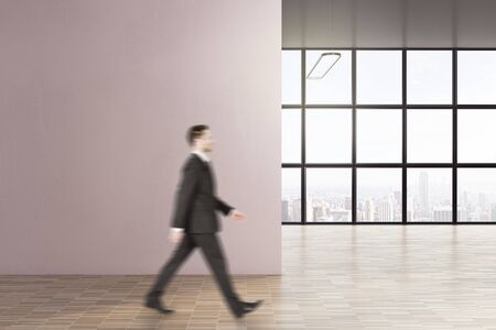 Businessman walking in modern interior with copy space on wall. Occupation and worker concept. Mock up