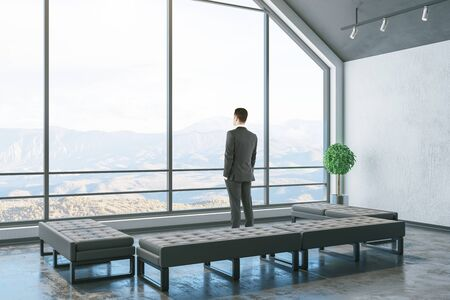 Businessman standinf in cozy attic interior room with bench and window with landscape view. Design and style concept. Zdjęcie Seryjne