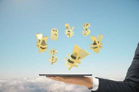 Businessman hand holding digital tablet with golden world currency signs on blue sky background. Business and financial success concept.