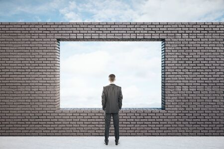 Businessman standing in empty interior with blue sky view. Business and success concept.
