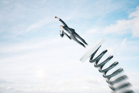Businessman in suit lauching off big spring on sky background with clouds. Startup and success concept