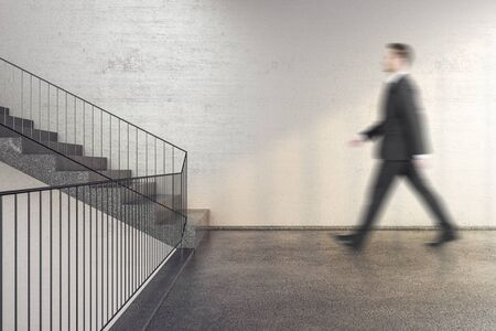 Businessman walking on stairs in office building with copy space on wall. Performance and presentation concept.