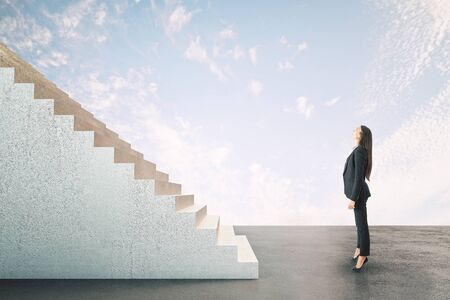 Businesswoman looking on abstract stairs on bright sky background. Career development and job concept Banco de Imagens