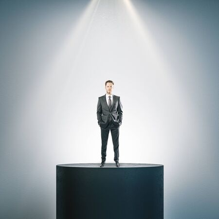 Businessman standing on illuminated pedestal in interior. Presentation concept. Stock Photo