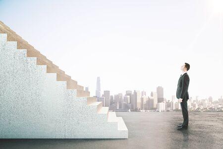 Geschäftsmann, der auf abstrakter Treppe auf hellem Stadthintergrund schaut. Karriereentwicklung und Stellenkonzept