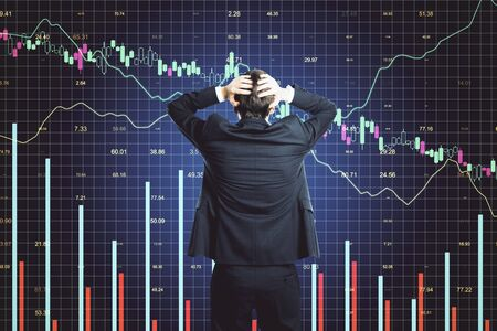 Scared businessman looking on glowing stock analytics on virtual screen. Global business and information technology concept Banque d'images