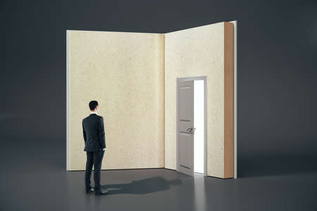 Businessman looking at abstract open book with door on gray background. Opportunity, education and business concept. 3D Rendering