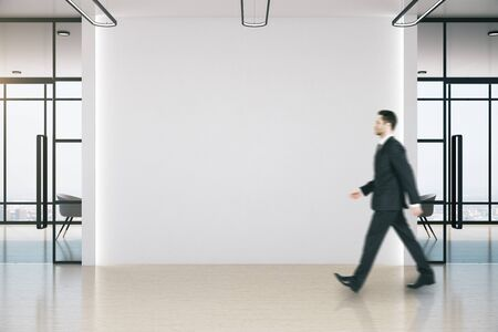 Businessman walking in meeting room with blank white wall. Occupation and worker concept.