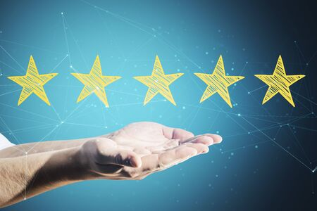 Hand holding star rating on blue virtual screen background. Evaluation and assessment concept