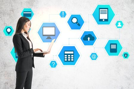Businesswoman using laptop and drawing cloud computing diagram on concrete wall. Business and technology concept. Stock Photo