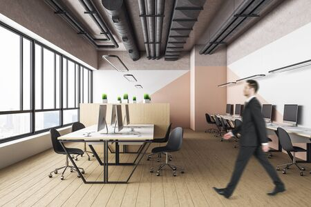 Businessman walking in office interior hall with computers and city view. Workplace and lifestyle concept. Imagens
