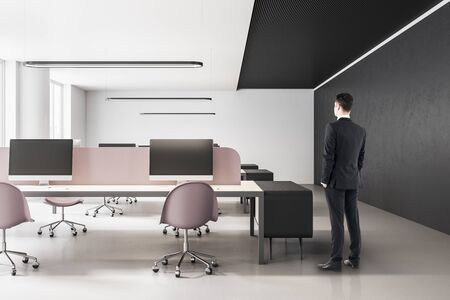 Young businessman standing in minimalistic office interior with computers. Workplace and lifestyle concept. Stock fotó