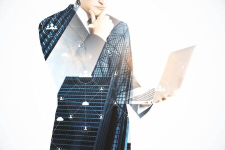 Businessman holding laptop computer on city background. Technology, network and communication concept. Double exposure