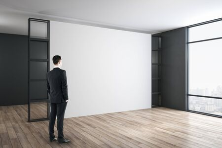 Businessman standing in modern gallery room with blank wall. Performance and presentation concept.
