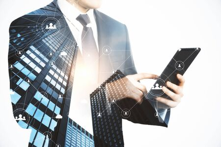 Businessman hands using pad on abstract city background. Technology, network and communication concept. Double exposure