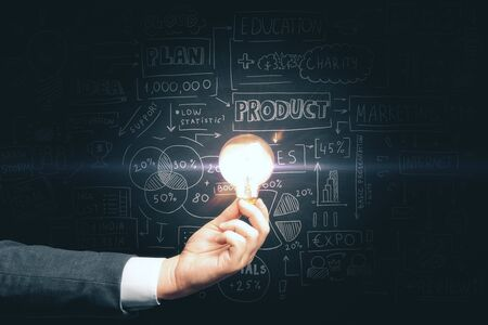 Mano de hombre de negocios sosteniendo la bombilla y dibujando un plan de marketing empresarial global. Concepto de análisis comercial y empresarial. Foto de archivo