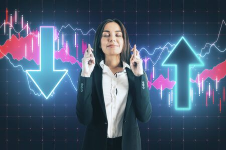 Businesswoman crossed her fingers for luck with  glowing stock analytics with arrow on virtual screen. Global business and information technology concept Stok Fotoğraf