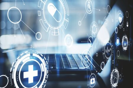 Blurry laptop with creative glowing blue medical hologram. Medicine technology concept. Double exposure Stock fotó