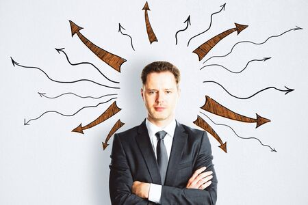 Businessman in suit with drawn arrows over her head on concrete wall. Leadership and way concept Stock Photo