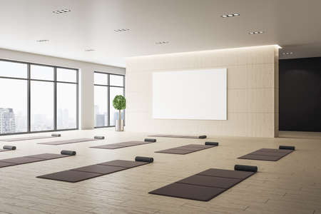Contemporary interior of yoga classroom with mats and blank banner on wall. Healthy lifestyle concept. Mock up. 3D Rendering