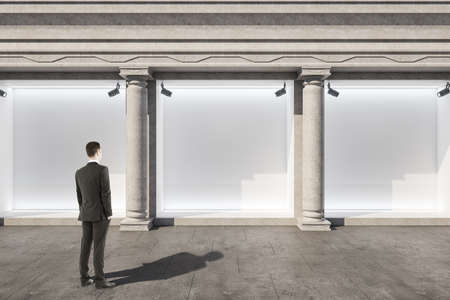 Businessman standing near shop window with blank poster. Advertisement and retail concept. Mock up,