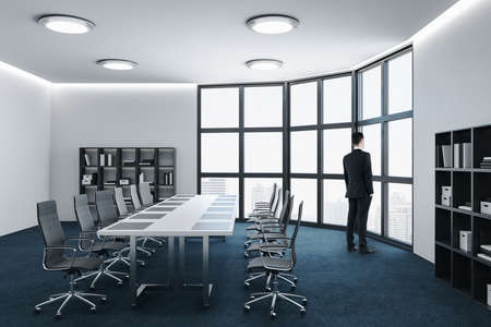 Businessman standing in conference room with panoramic city view and daylight. Business and corporate concept. Zdjęcie Seryjne