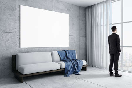 Businessman standing in living room with sofa and blank poster on wall. Art and design concept. 免版税图像