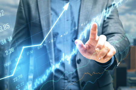 Businessman hand pointing at stock chart screen interface with data. Trade and finance concept. Double exposure