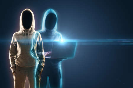 Two hacker in hoodie with laptop on blue background. Cyber security and identity theft concept. 免版税图像