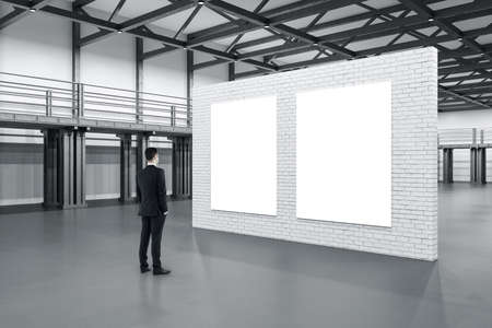Businessman standing in showroom with exhibition brick stand with two blank posters. Design and style concept. Mock up,